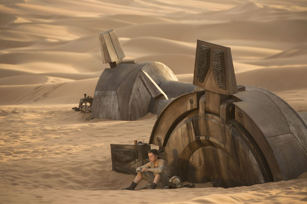 Screenshot from The Force Awakens: Rey sits outside in the desert at sunset next to the toppled ruins of a metal armature.