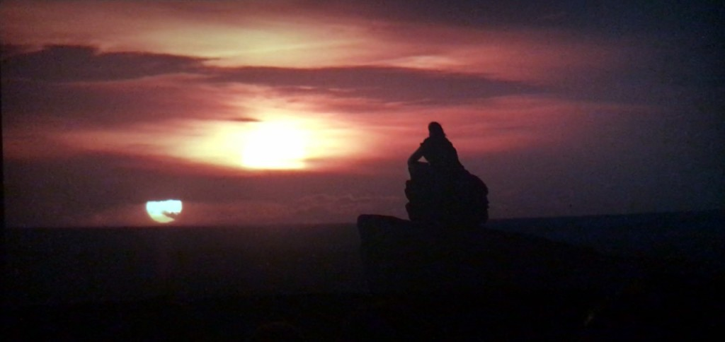 Screenshot from The Last Jedi: A seated figure, Luke, silhouetted against twin setting suns.